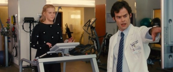 Schumer (on the machine) flirts with the good Doctor (Bill Hader).